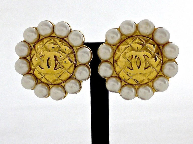 Vintage Massive CHANEL Quilted CC Logo Pearl Earrings  Measurements: Height: 1.6 inches (4 cm) Width: 1.6 inches (4 cm)  Features: - 100% Authentic CHANEL. - Gold tone with quilted CC logo surrounded with 12 lustrous faux pearls - Gold tone