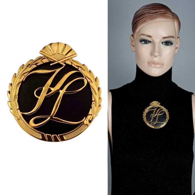 Vintage Massive Iconic KARL LAGERFELD KL Logo Fan Medallion Brooch  Measurements: Height: 3.38 inches (8.6 cm) Width: 3.11 inches (7.9 cm)  Features: - 100% Authentic KARL LAGERFELD. - Embossed KL initials at the center. - Ornate leaves and fan