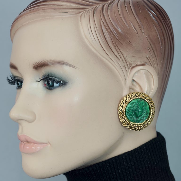 Vintage Massive KALINGER Cherub Carved French Earrings  Measurements: Height: 1.57 inches (4 cm) Width: 1.57 inches (4 cm) Weight per Earring: 19 grams  Features: - 100% Authentic KALINGER. - Disc earrings with carved cherub on a green resin. - Gold