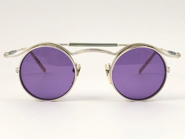 Cult brand Matsuda signed this ultra chic pair of silver matte frame with a beautiful pair of medium purple lenses.   Superior quality and design.   This item show minor sign of wear due to storage.  MEASUREMENTS   FRONT : 13 CMS  LENS HEIGHT : 41