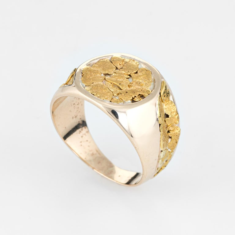 Vintage men's nugget signet ring (circa 1970s to 1980s), crafted in 10 karat yellow gold.   The gold nuggets are set in random from into the round signet mount and side shoulders. With a low profile and slightly curved saddle the ring sits