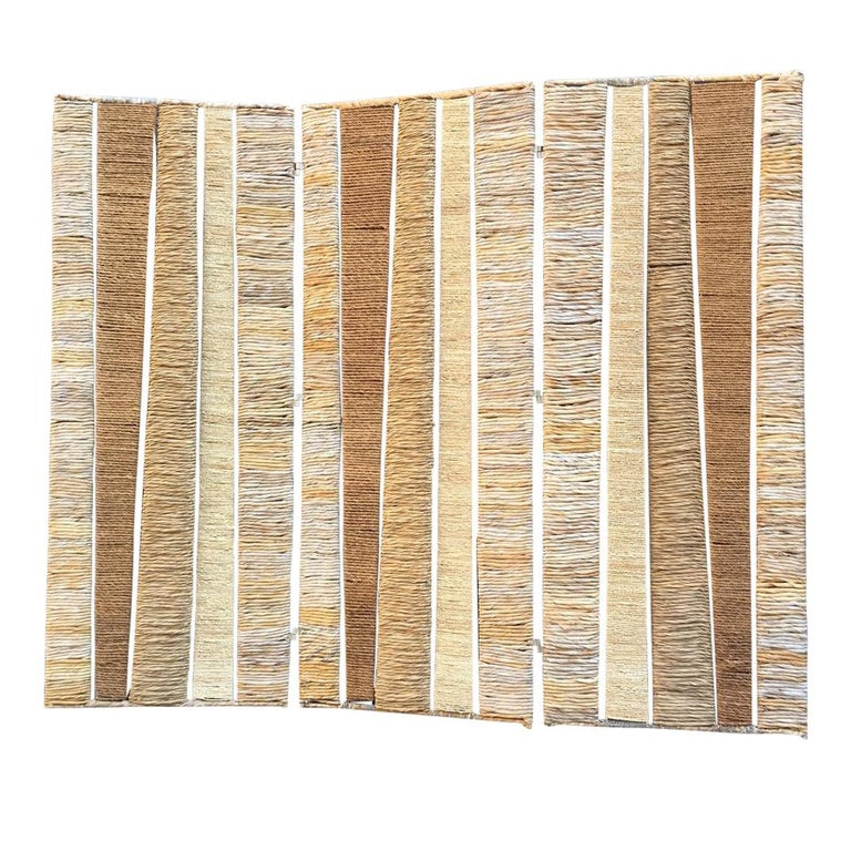 This abstract design folding screen consists of 3 folds, each fold features enameled metal big frame with smaller frames inside - rope, wicker and straw on them. There small black plastic legs. It is very heavy and stable.  This room divider has