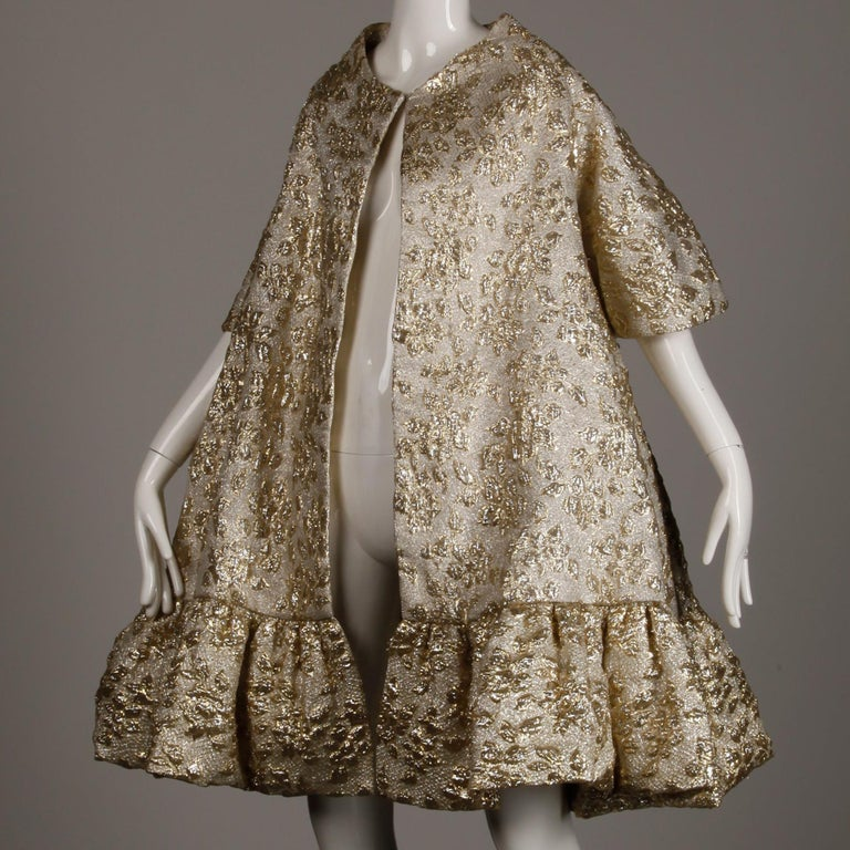 Dramatic 1960s vintage metallic gold lamé swing coat by Mam'selle by Betty Carol. Huge sweep with so much fabric and A-line shape. Fully lined with front hook closure. Fits most modern sizes small-large on account of the free shape. The bust