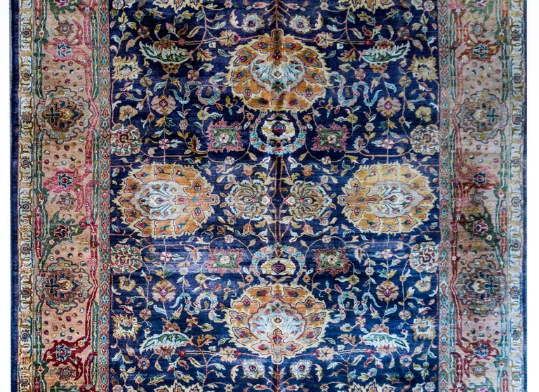 A fantastic mid-20th century Indian Sultanabad style rug with a beautiful large-scale mirrored floral pattern with four large medallions amidst scrolling vines and myriad flowers on a dark indigo background. The border is really wide with a