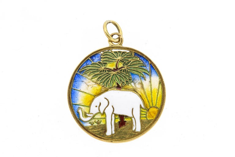 A charming vintage 18k yellow gold and enamel elephant charm with colorful plique-a-jour background circa 1950. The charm has French hallmarks. The elephant has its trunk held up which is a symbol of good luck. The charm is double sided, so the