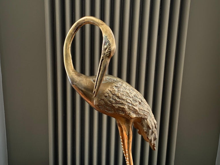 Vintage 1970s brass crane with a curved neck and sculpted plume of feathers. The crane is stood on a rectangular base to help keep it stable and upright. In excellent vintage condition with a deep, aged patina. An interesting and decorative piece
