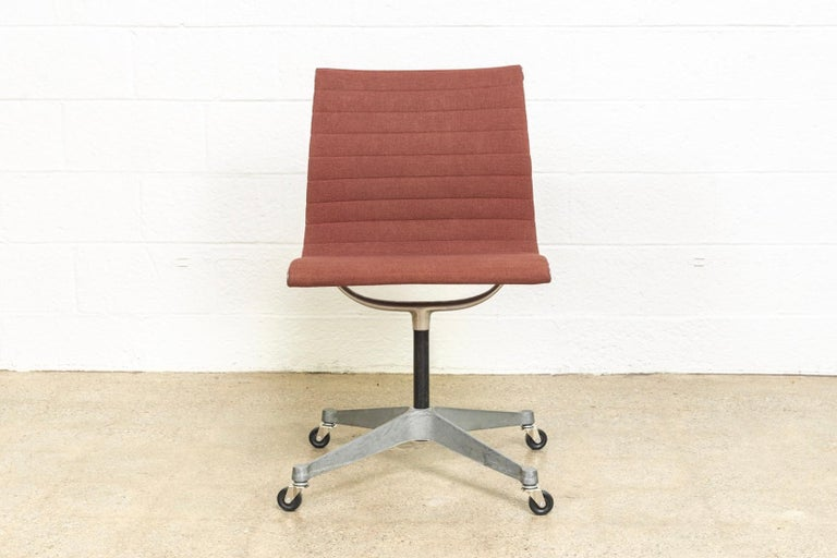 This vintage Classic Charles and Ray Eames for Herman Miller Aluminum Group Management side chair has a clean and refined design with curvilinear lines and elegant profile. It features a cast aluminum frame and 4-star contract base with rolling