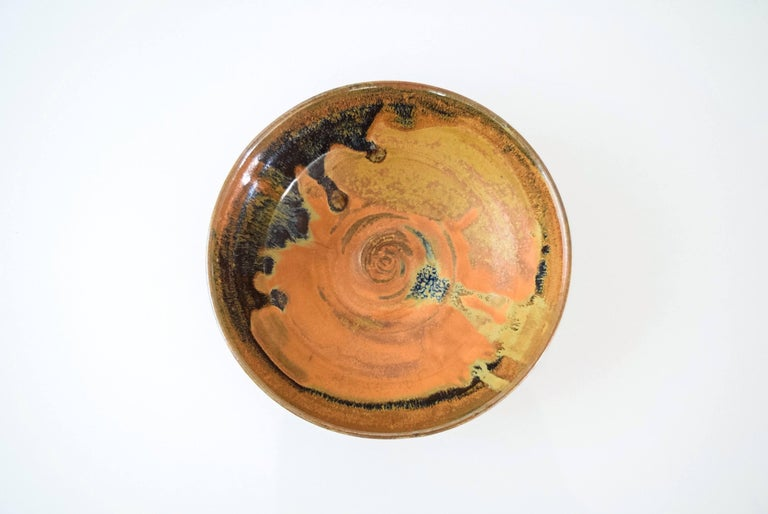 This vintage Mid-Century Modern ceramic pottery bowl is circa 1960. It features a simple modernist handcrafted design with beautiful shades of natural burnt orange, gold, blue and black in varying sheens.  Dimensions: Diameter 7 1/8