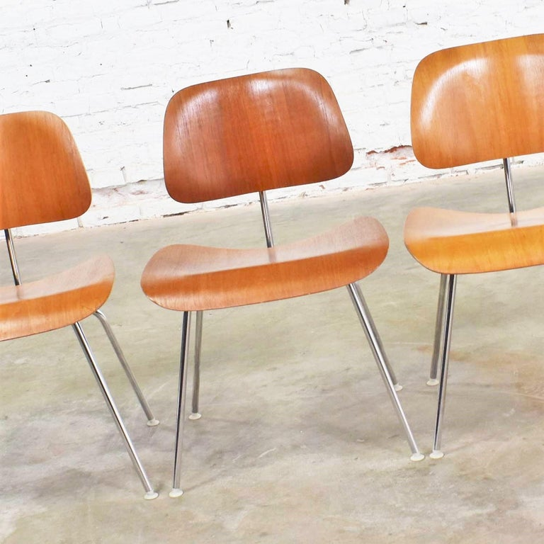 Handsome set of 4 vintage Mid-Century Modern Eames DCM, dining chair metal, dining chairs for Herman Miller with silver colored bases, white nylon feet, and walnut veneer. They are in overall wonderful vintage condition. There are some small flaws