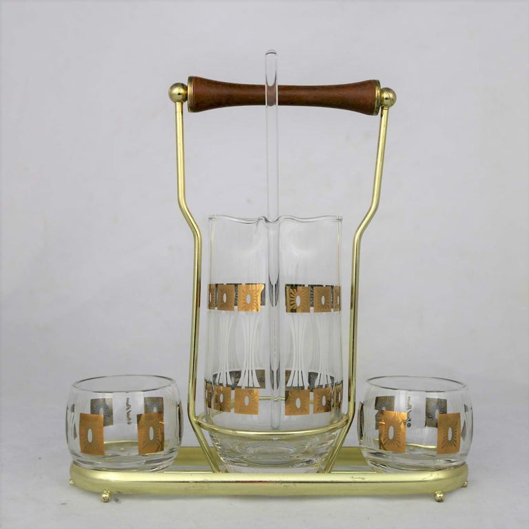 Handsome Mid-Century Modern cocktail caddy set by Fred Press in his sun block pattern. Comprised of a signed cocktail carafe with glass stirrer and two signed roly poly glasses in a brass plated carrier. They are all in fabulous vintage condition