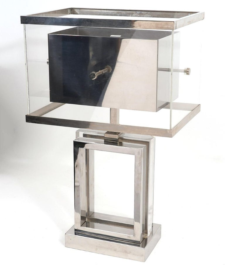 Vintage Italian chrome and Lucite Mid-Century Modern table lamp by Romeo Rega. The base structure features a rectangular Lucite block between open chrome frames resting on a chrome base. The shade is made of clear Lucite with chrome edges and with