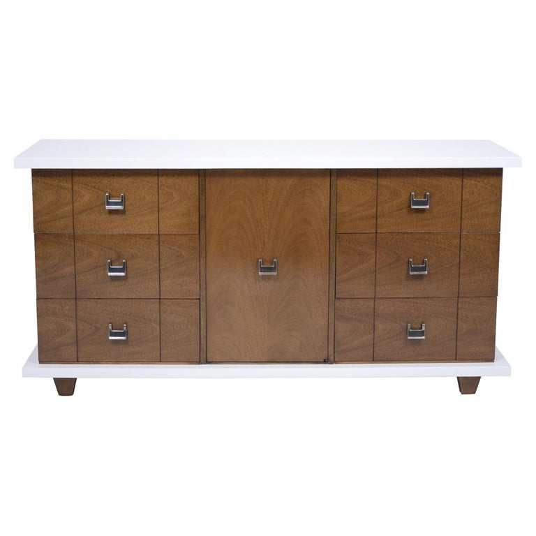 An extraordinary 1960s mid-century modern chest of drawers that has been professionally restored. is handcrafted out of walnut wood newly stained in an elegant white and walnut color combination with a lacquered finish. This fabulous credenza