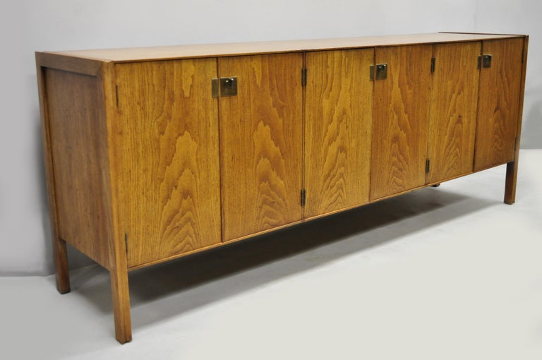 Vintage Mid-Century Modern oak credenza cabinet long buffet after James Mont. Item features beautiful wood grain, distressed finish, 6 swing doors, 3 dovetailed drawers, 3 adjustable shelves, solid brass hardware, clean modernist lines, quality