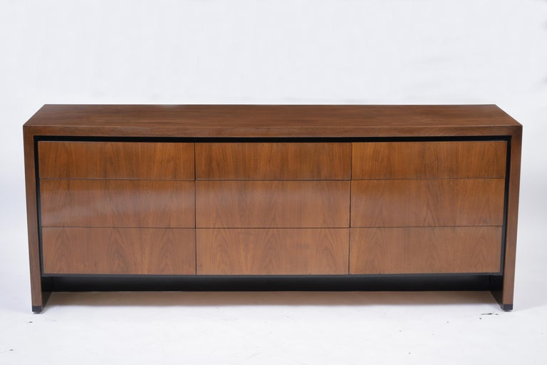 A modern 1960s chest of drawers handcrafted out of walnut wood features a dark walnut and ebonized color combination finished in a beautiful new lacquered finish. The dresser comes with nine pullout drawers with plenty of interior storage space that