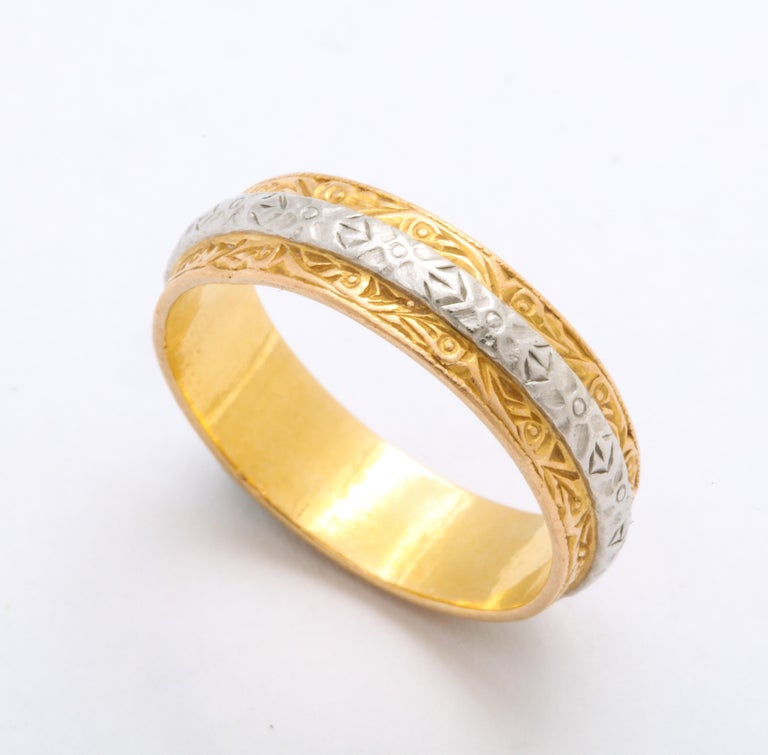 In chased 22 Kt gold with a platinum band around the center, this ring, by Charles Green and Son is as elegant, simple, and comfortable on the finger. The gold is adorned with scrolls and foliate details. The ring is a delight worn alone or perfect