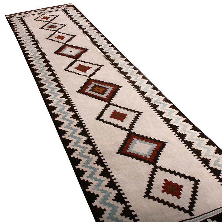 Handwoven in wool originating between 1950-1960, this vintage midcentury Persian Kilim runner hails from the Saveh region of West Persia, acclaimed for a particularly fine wool with a notable sheen distinguishing the most venerated items of the