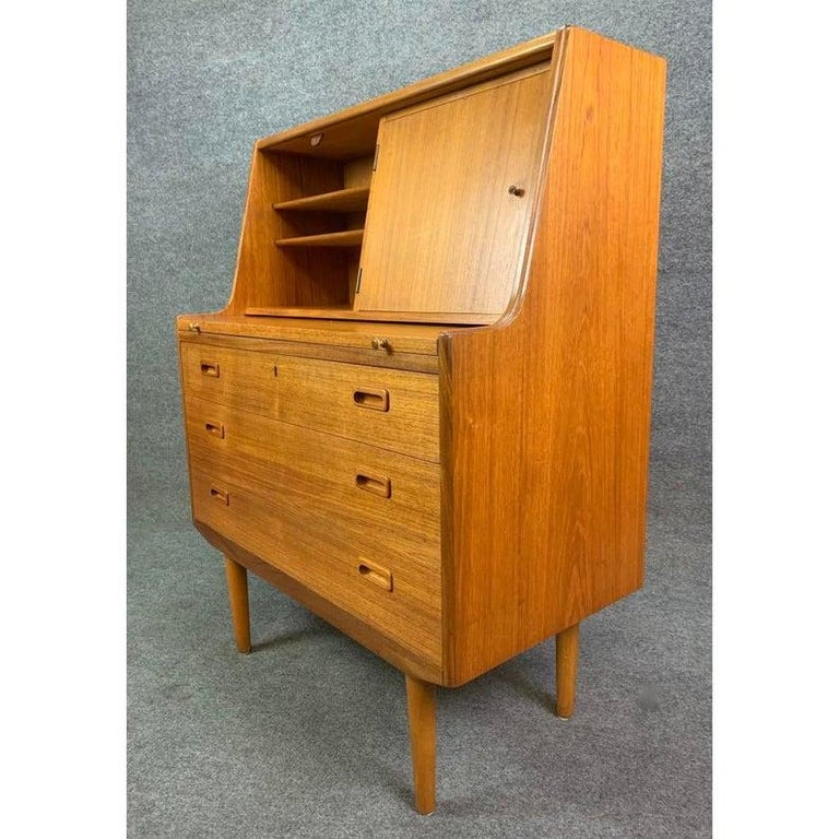 Here is an elegant secretary with a pullout / pull-out desk in teak wood recently imported from Sweden to California. This lovely pieces a very nice vibrant wood grain and features on its upper side two cubbies with shelving (one hiding behind a