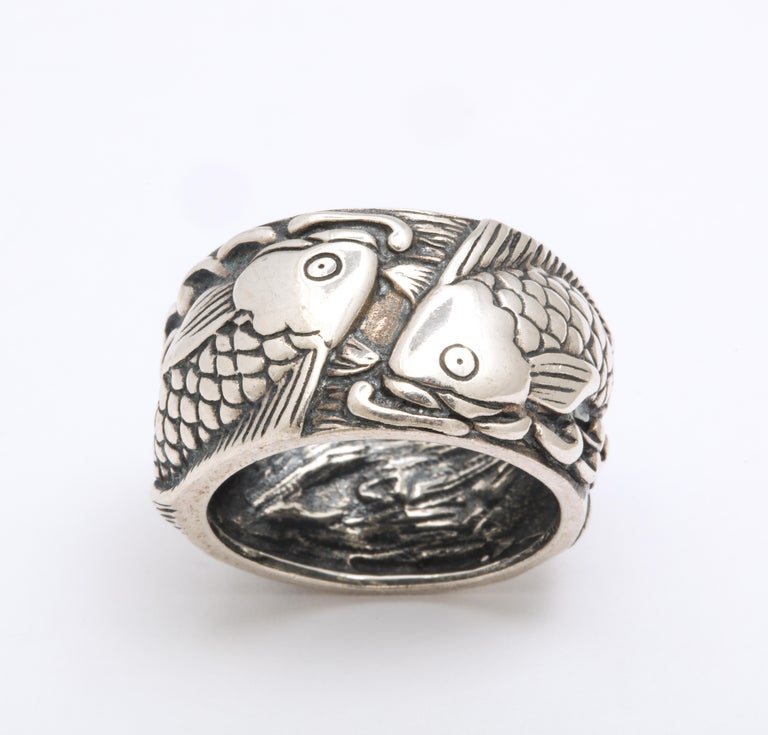 This is a mid century silver Pisces ring that is crisply engraved with so much detail and whimsy that I can't help but smile One does bot have to be a Pisces to enjoy the fun of this ring. Two fish splash their way through the waves. The splashes