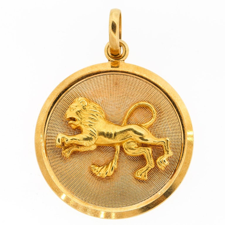 A round 18k gold mid-century Zodiac Leo disc charm. The charm depicts a dimensional lion in motion on the front of the charm. The lion is on a textured fluted gold background with a smooth frame around the charm. It is suspended by a large bail,