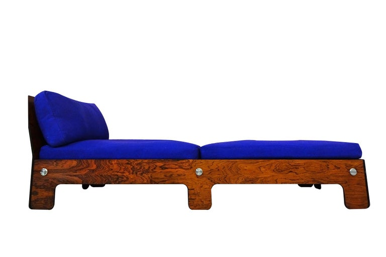 A very rare Midcentury chaise longue or day bed in blue and rosewood.  Very little is known about the designs origins of this beautiful and unusual chaise. The striking design using rosewood veneer complimented by large polished steel screw/bolts