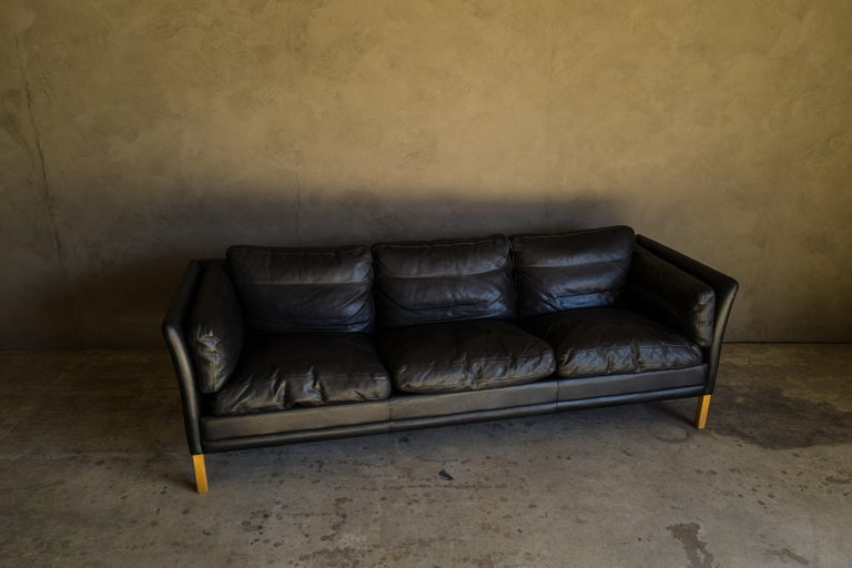 Vintage midcentury leather sofa from Denmark, circa 1980. Original black leather upholstery with light patina and wear.