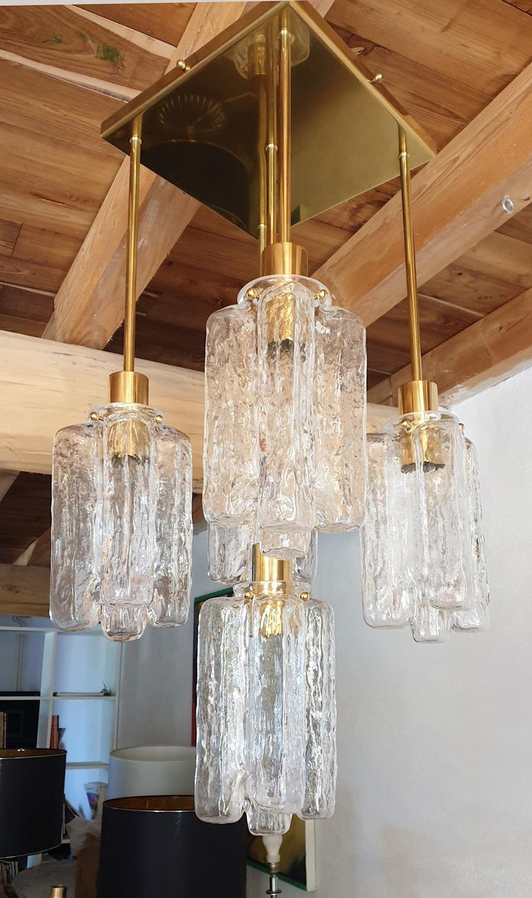 Handmade clear textured Murano glass and polished brass, 5-light flush mount ceiling light, attributed to Kalmar, Austria, 1960s. The ceiling plate is square, with 4 pendants, at different heights at the 4 corners, and the longest pendant at the