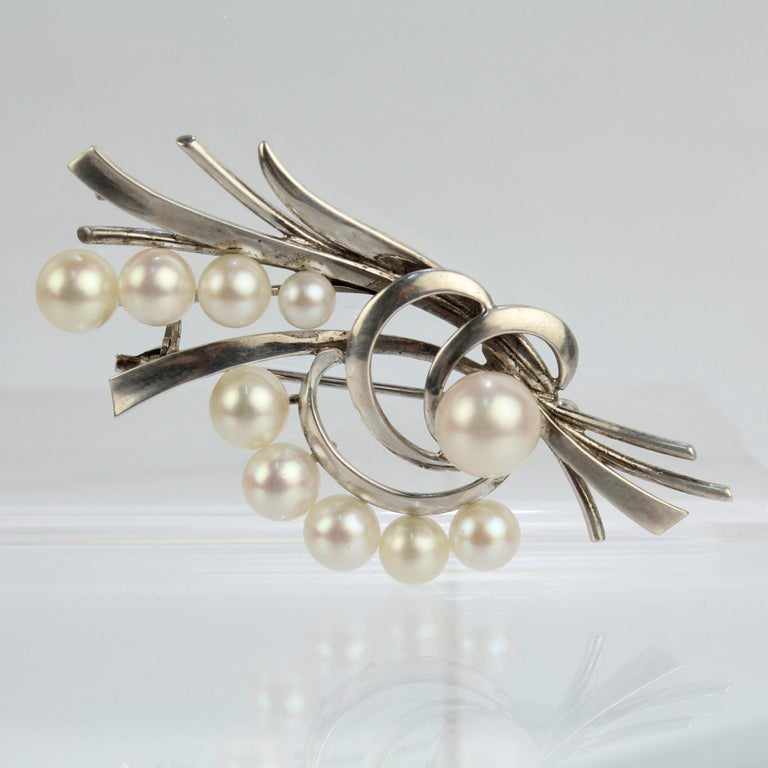 A very fine vintage Mikimoto Akoya cultured pearl and sterling silver brooch or pin.  With graduated round white pearls set on sterling silver bouquet-like stems.  Simply a fine brooch from the legendary Mikimoto!  Date: 20th Century  Overall