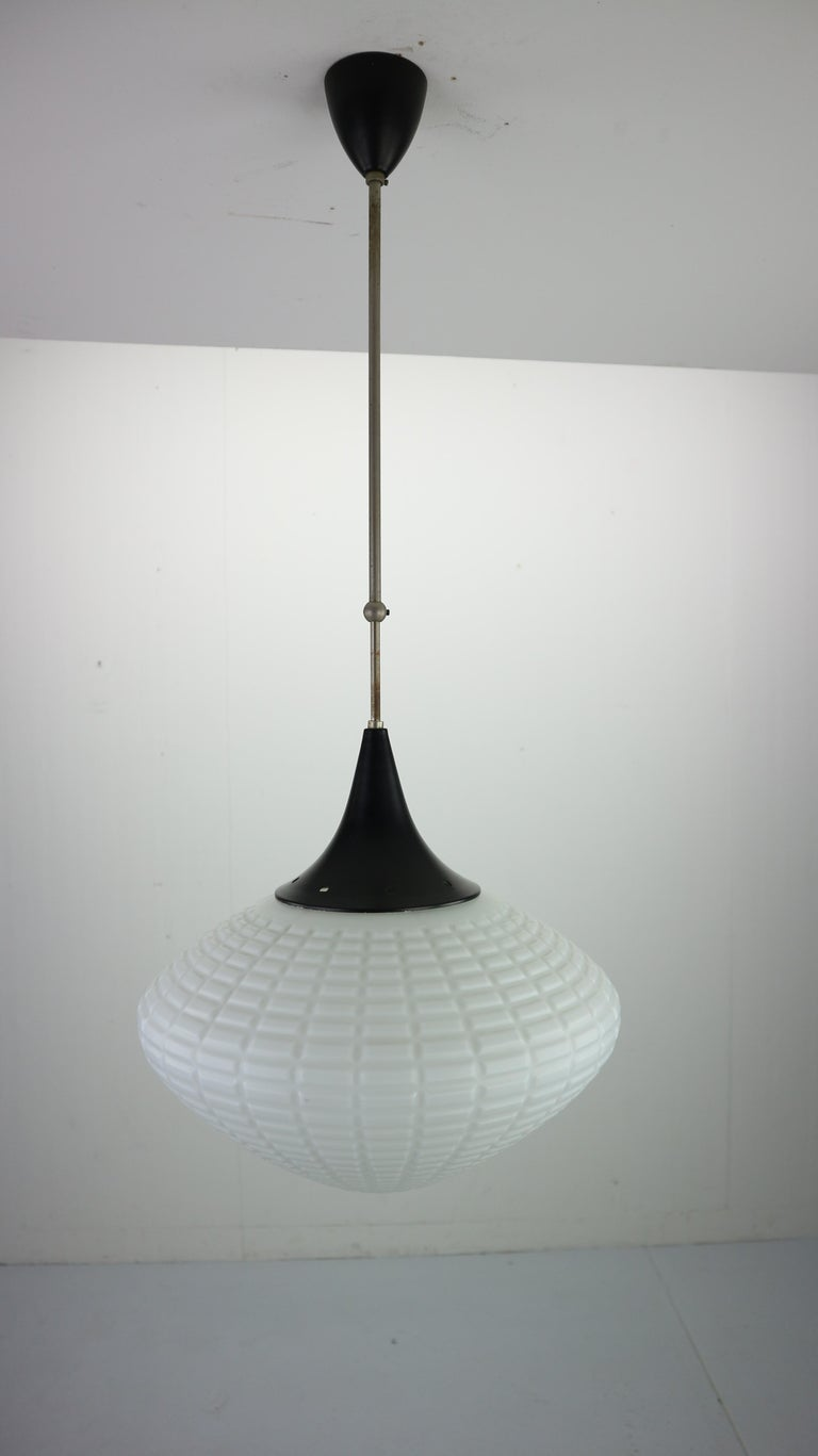 Made in the 1950s by Kamenický Šenov, Czechoslovakia.  An elegant vintage pendant lamp. The lamp shape reminds of the water drop and it's made of the curved white milk glass attached to a metal frame. Art Deco style, made in 1950s in it's original