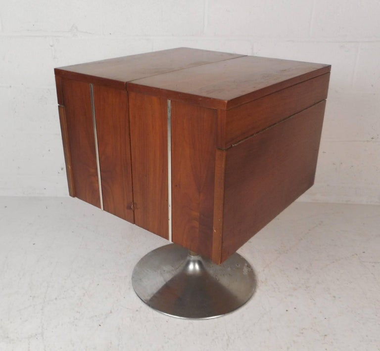 An amazing midcentury small mini bar by Lane! This compact bar opens up to unveil a 15 inch deep bar stash area with a drop in shelf. The top turns into a small table with a black laminate top meant to place cups on each side. Chrome strips on two
