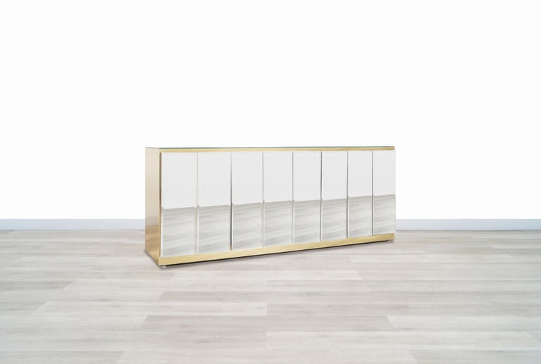 Beautiful vintage mirrored and brass credenza designed by Ello Furniture in United States, circa 1970s. This credenza or sideboard features four doors that are made up of elegant mirrors with beveled edges that offer a different touch to the view.