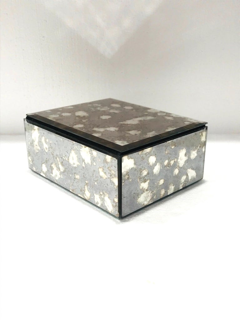Vintage Hollywood Regency decorative box. The mirrored box captures the beautiful gradient movement of agate stone with antique spotted glass in hues of grey and bronze. The box features beveled edges with a hinged lid and a black felt interior and