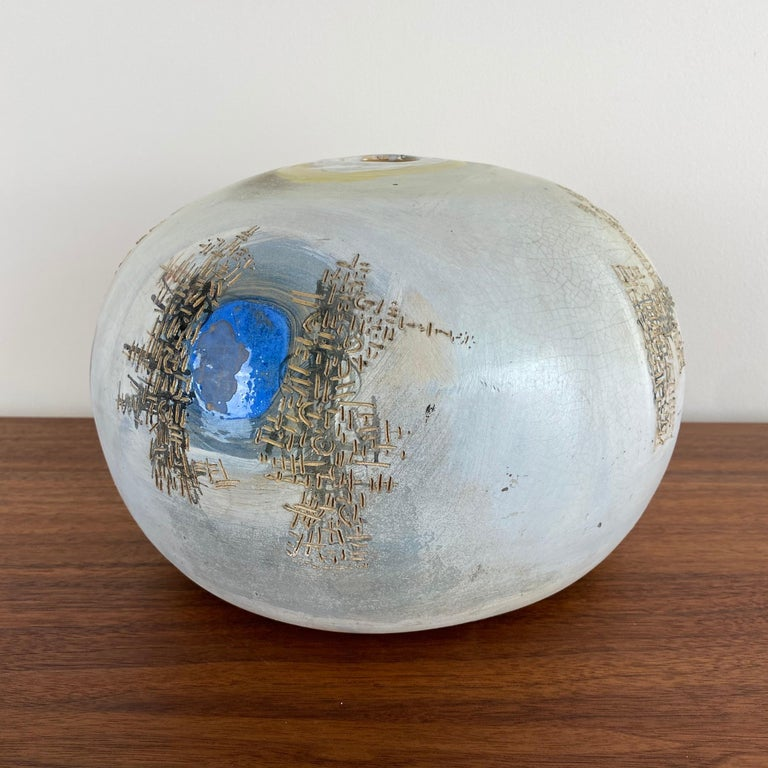 This bulbous vase has a soft blue glaze with abstract designs around the body. Multi-colored with texture and movement.