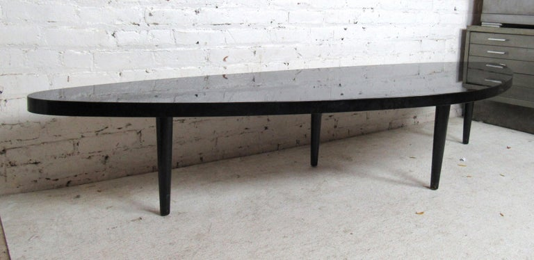 Unique Mid-Century Modern black laminate coffee table features four tapered legs and an odd shaped top.