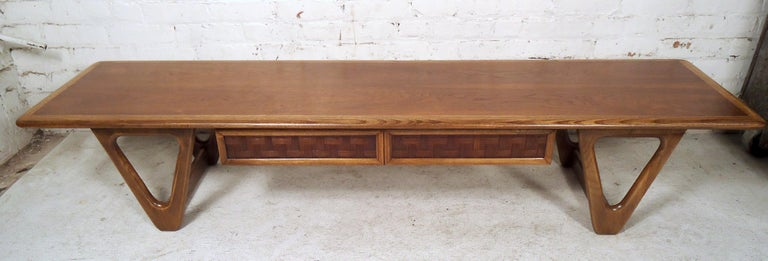 Stylish midcentury coffee table by Lane Furniture Company, circa 1960s. Ample table surface area, uniquely sculpted legs, one drawer under the tabletop with an interesting woven pattern on the drawer-front.