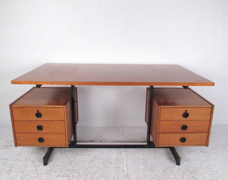 This stylish Italian modern desk features quality teak construction, floating top design, and six drawers for plenty of storage. Unique drawer pulls and midcentury design add to the vintage charm of this impressive writing desk, perfect for home or