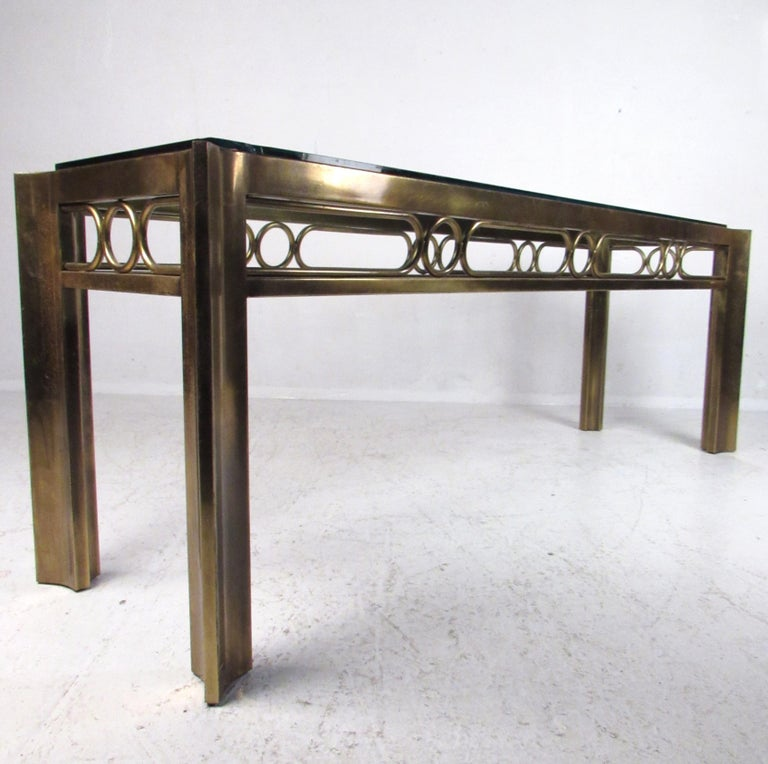 This elegant Mid-Century Modern hall table features a decorative brass frame with an unusual shape. This sleek and heavy console table by Mastercraft boasts a wonderful patinated finish. A thick glass top with beveled edges rests comfortably on the