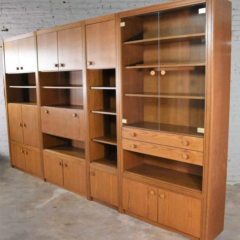 Handsome and versatile Scandinavian Modern style oak four section modular wall unit from the Lord series by Kämper Anbaumöbel. It is in wonderful vintage condition. Not without signs of age but nothing outstanding. There are a couple repairs which