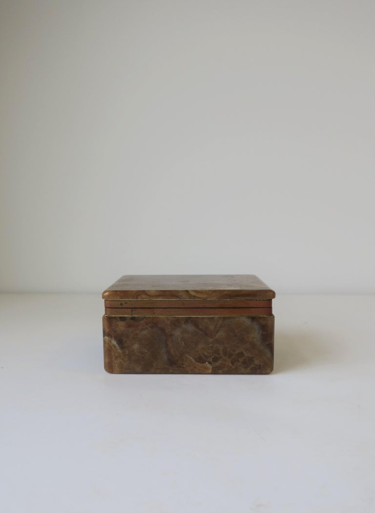 A very beautiful, substantial and chic Belgian Modern brown, caramel, and white onyx marble and brass hinged box, circa early 20th century, Belgium. Box is rectangular in shape and can hold jewelry (as demonstrated) or other small items on a desk,