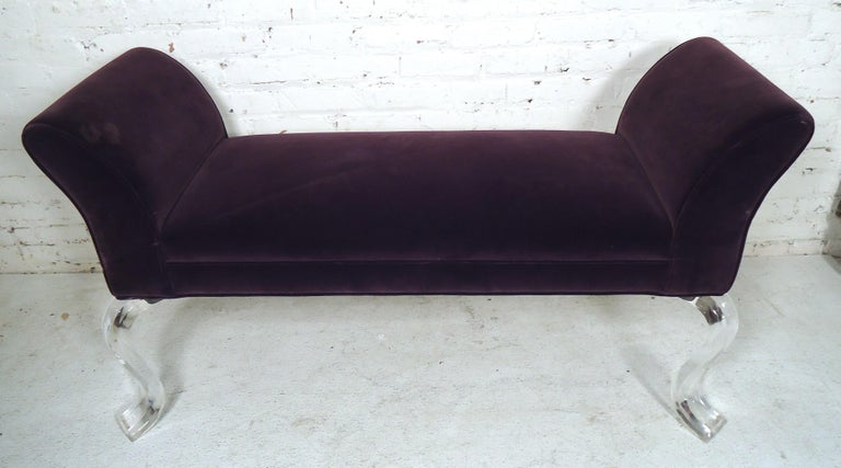 This Mid-Century Modern style bench is featured in purple upholstery on a set of curved Lucite legs, can be used as an entry way or bedroom bench.