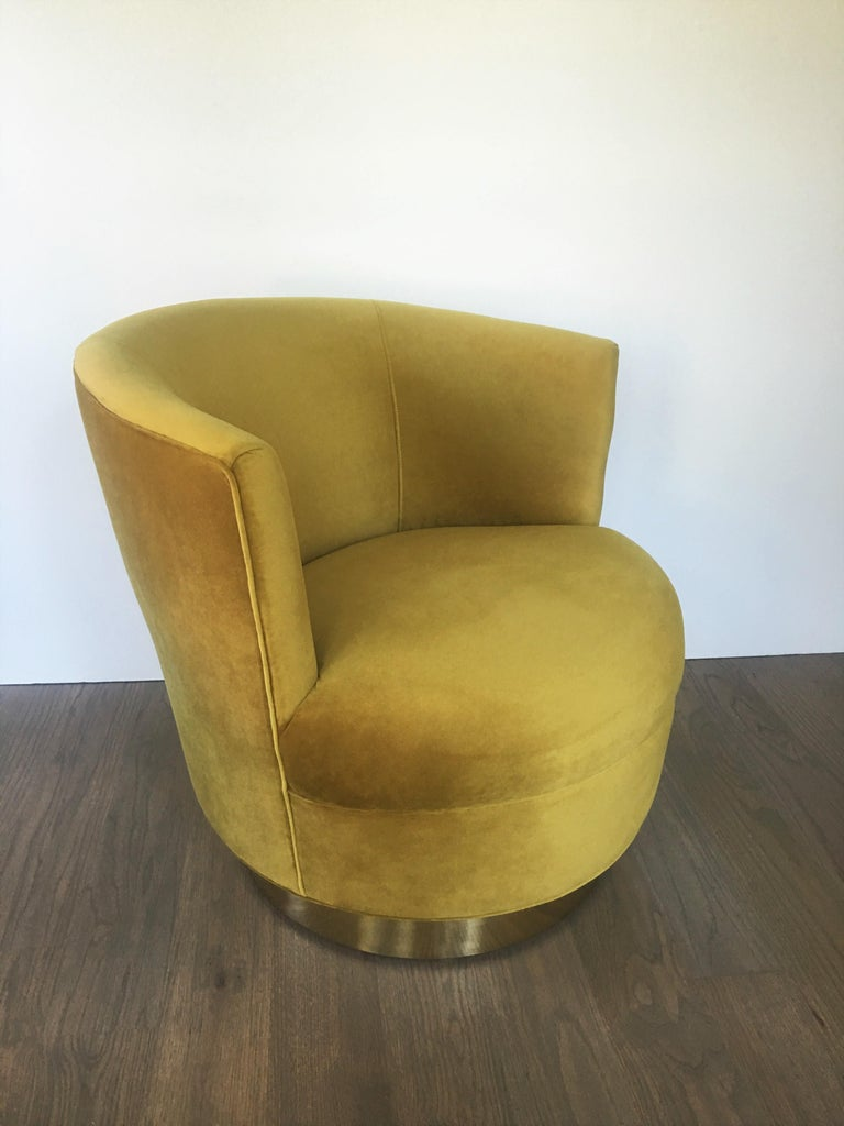 Stunning pair of swivel lounge chairs, recently recovered in a gold colored velvet. Features clean modern lines, barrel backs with the uppers raised on swivelling brass trimmed plinths.