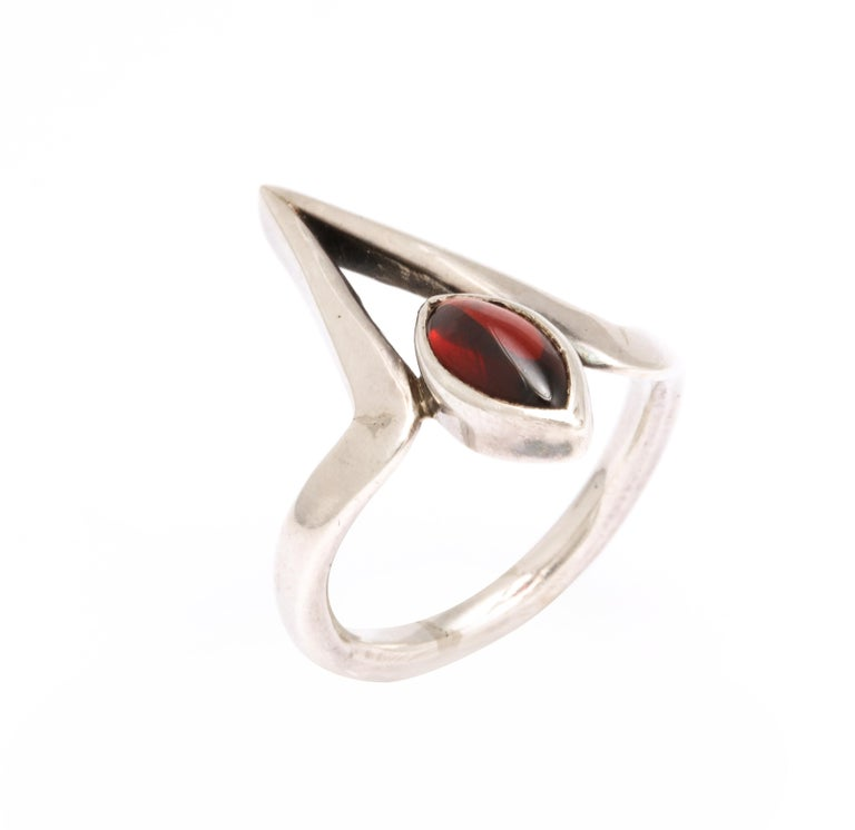 We offer a striking asymmetric ring design in silver and garnet made by Jack Nutting, a modernist sculptor and jewelry designer. The oval garnet, deeply set in a substantial silver collet, rests with grace in a triangular pagoda. The ring is one