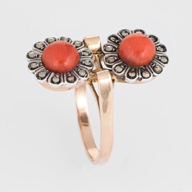 Finely detailed vintage coral & marcasite double flower ring (circa 1950s to 1960s) crafted in 18 karat yellow gold.   Two pieces of coral each measure 5.7mm, accented with marcasite.      The charming double flower motif represents two lives joined