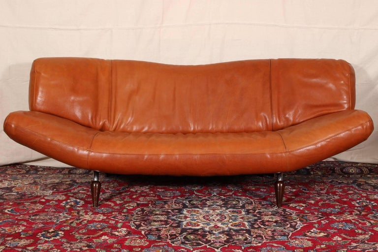Vintage Molinari tobacco leather sofa, curved back and seat with adjustable arms (the right one does not lock into place when adjusting). Raised on chrome topped dark wood round tapering splayed legs in front and chrome wheeled ones at back.
