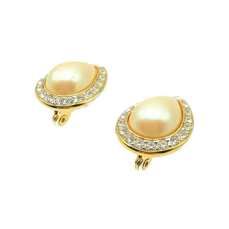 A Vintage Monet Pearl Teardrop Earring. Crafted in gold plated metal set with a glass teardrop faux pearl and crystals. Very good vintage condition, 2.2cms, signed.  Established in 2016, this is a British brand that is already making a name for