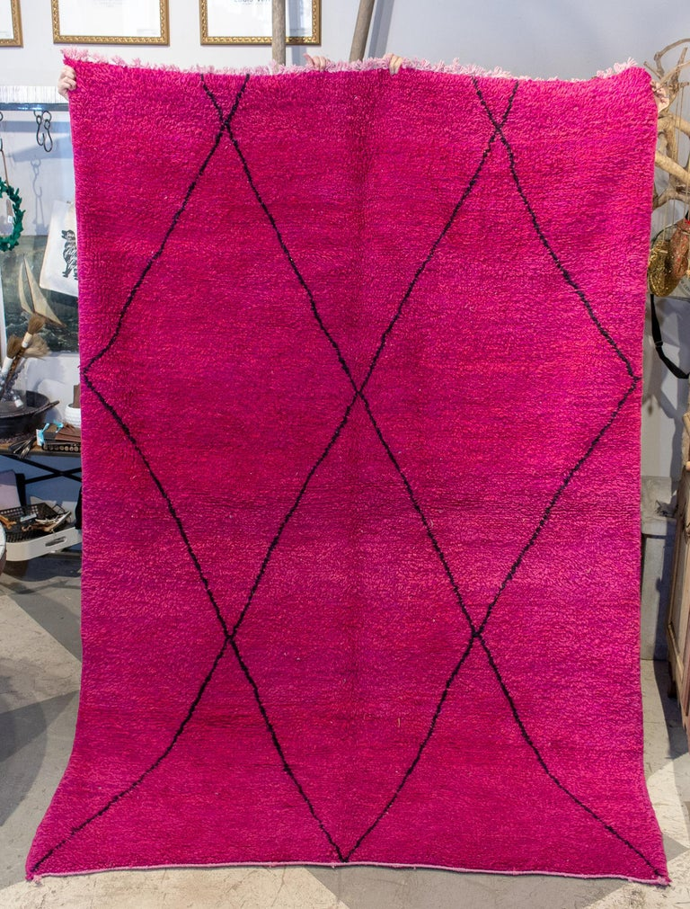 This is a Moroccan Beni Ourain Berber rug sourced in Marrakech. This rug features a hot pink and fuchsia background with black-diamond patterning, as is typical of these rugs. This rug is handmade and features two sides, one flat-woven side for