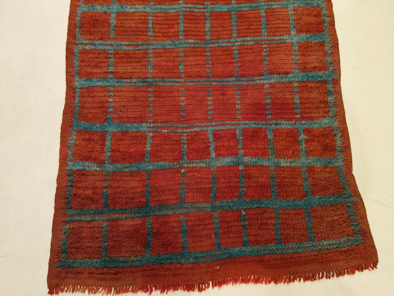 An old and genuine Moroccan Berber rug from the Middle Atlas region distinguished by a light blue square grid network on a brick orange background. The particularly narrow width makes this narrow especially ideal for the width of today's hallways