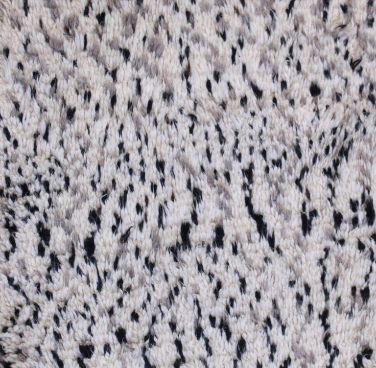 This authentic Azilal carpet is hand knotted with a blend of subtle browns, gray and black on a field of ivory white wool. Azilal carpets take on a very abstract and lively linear quality. The patterns woven into these carpets are a combination of
