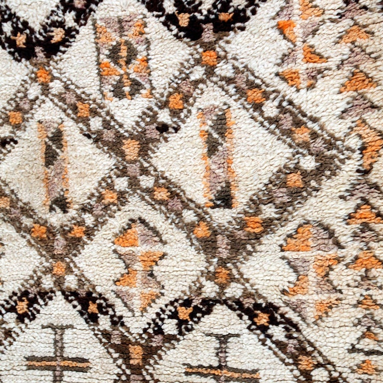 A wonderful array of subtle browns, with accents of faded purple and henna orange on a natural field of wool. Berber tribes produce some of the finest quality rugs in all of Morocco. These rugs show an archaic symbolism that dates back to the