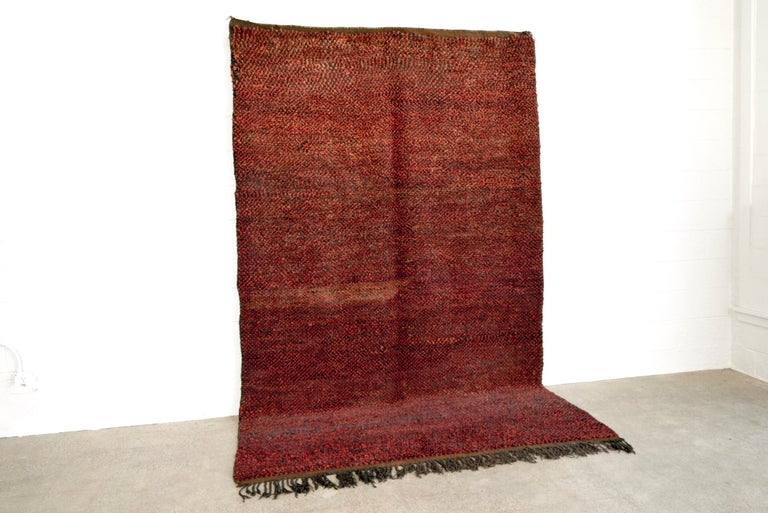 This large, richly-colored vintage Moroccan Berber rug is composed of handwoven dark red and black wool strands which combine to create a gorgeous field of deep cranberry with beautiful depth and color variation. The thick wool pile is full and soft