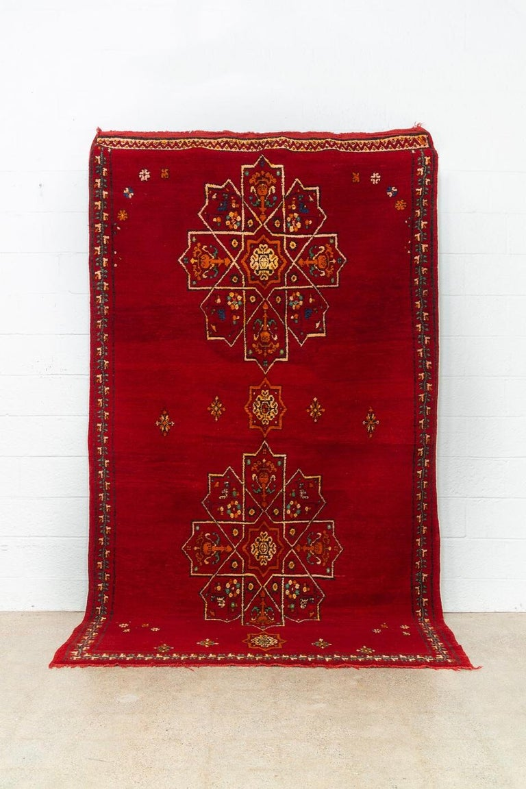 This stunning large vintage handwoven Moroccan Berber rug circa mid-20th century is a beautiful combination of hand knotted pile and embroidery. The design features a large symmetrical arabesque pattern on a gorgeous field of crimson red with accent